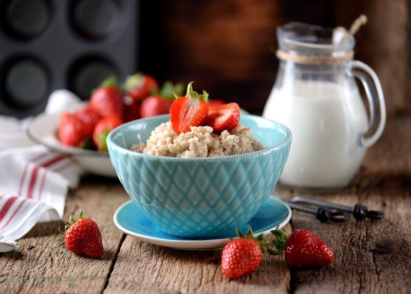 Farine d'avoine avec les fraises et le lait frais sur un vieux fond en bois Nourriture saine de petit déjeuner sain photo stock
