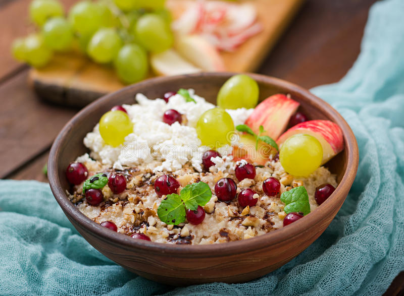 Farine d'avoine délicieuse et saine avec des raisins, des écrous, des pommes et le fromage blanc photos libres de droits