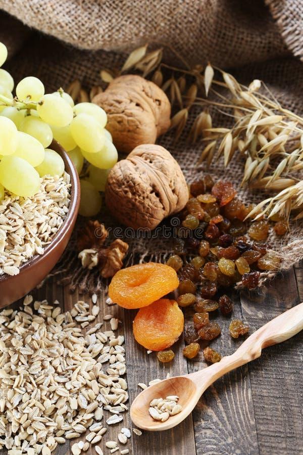 Farine d'avoine dans une cuvette d'argile, tiges d'avoine, abricots secs, raisins secs, image stock