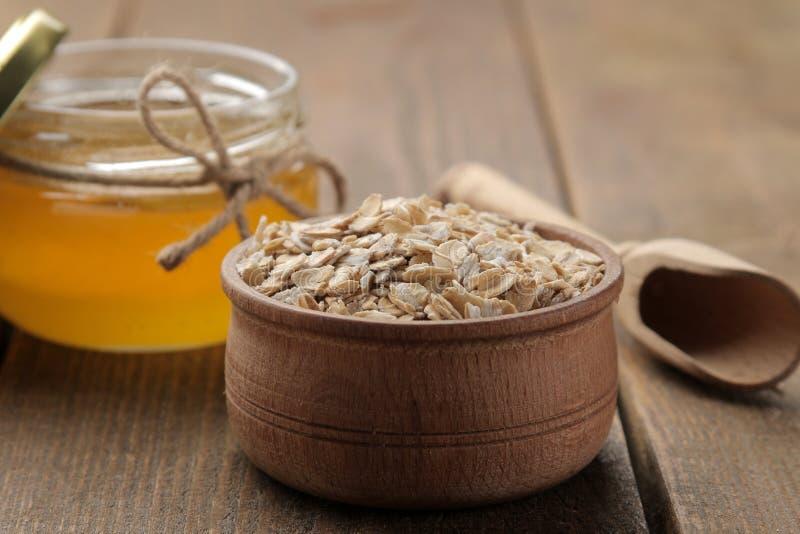 Farine d'avoine sèche dans une cuvette et un miel en bois Nourriture Nourriture saine Sur une table en bois brune photo stock