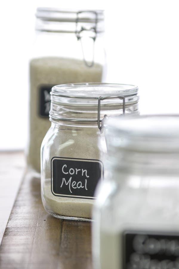 Farine de maïs dans un pot avec d'autres ingrédients de cuisson dessus hors de fond de foyer photos libres de droits
