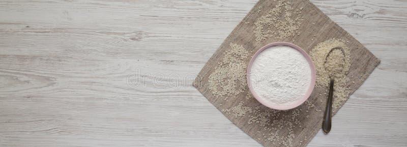 Farine de riz libre de gluten dans une cuvette rose au-dessus de la surface en bois blanche, vue supérieure Configuration plate,  photographie stock libre de droits