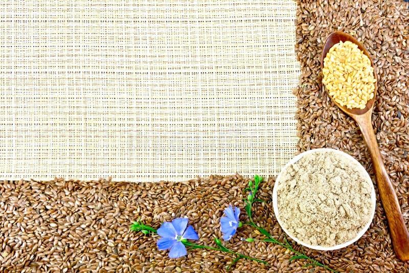 Farine et graines de lin avec des fleurs sur le textile tissé brut photo libre de droits