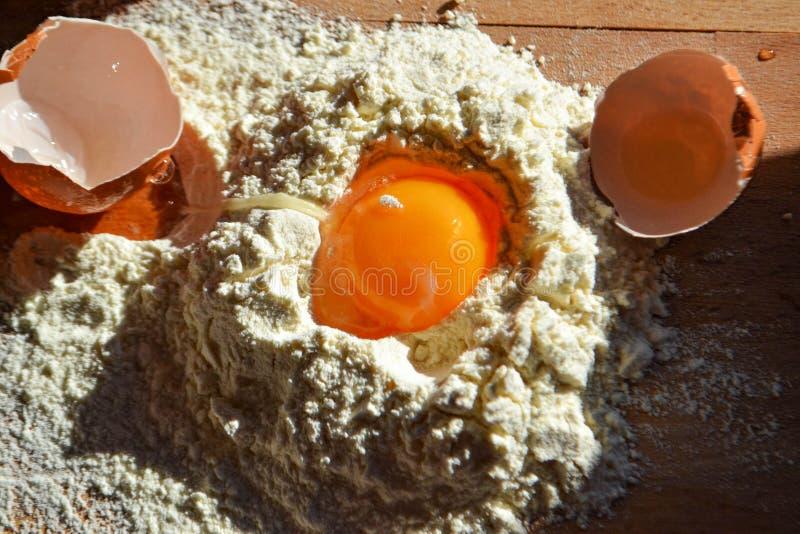 A farinha branca com ovos, a manteiga e a colher de madeira em um cozimento embarcam foto de stock