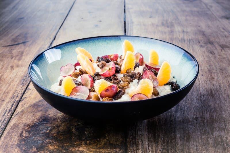 Farinha de aveia caseiro com canela, uvas, segmentos alaranjados na bacia do vintage fotografia de stock