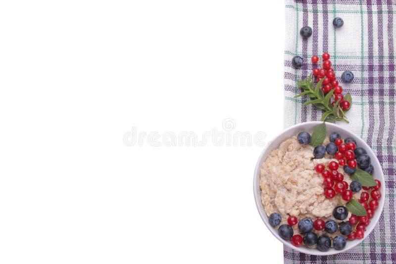 Farinha de aveia com as bagas no fundo isolado branco Alimento saudável do café da manhã fotos de stock royalty free
