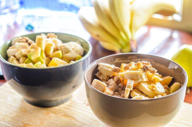 Farinha de aveia com banana, laranja, Apple verde, as nozes, o sésamo e o Chia Seeds imagens de stock