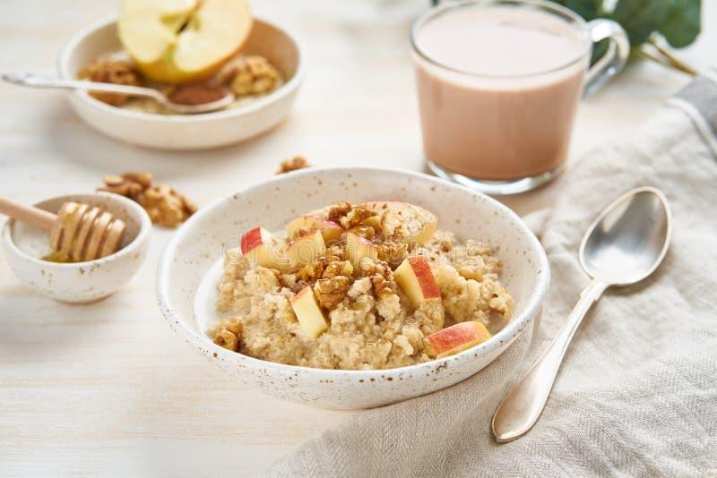 Farinha de aveia com maçã, nozes e copo do cacau no fundo claro de madeira branco Vista lateral Pequeno almoço da dieta saudável fotos de stock