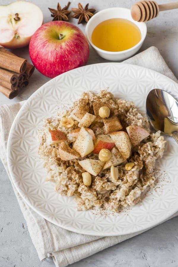 Farinha de aveia com maçãs, as porcas e canela frescas para o café da manhã na tabela, close-up, vertical fotografia de stock royalty free