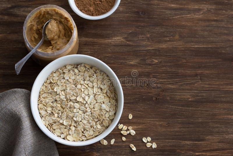 Farinha de aveia crua em uma bacia branca com manteiga de amendoim e cacau ingredientes para um papa de aveia delicioso do chocol imagem de stock royalty free