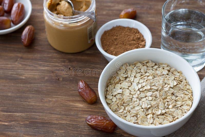 A farinha de aveia crua em uma bacia branca, data frutos, manteiga de amendoim, cacau e um vidro da água, ingredientes para o caf foto de stock