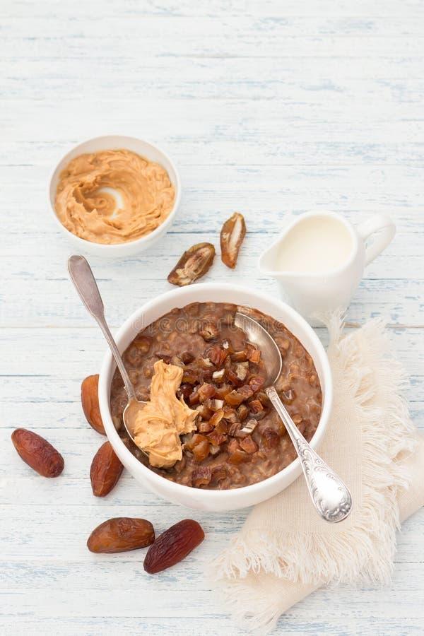 A farinha de aveia deliciosa em uma bacia branca, data o leite dos frutos, do cacau e do vegetariano fotografia de stock