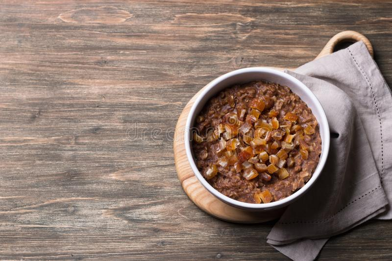 Farinha de aveia deliciosa em uma bacia branca, em frutos das datas e em cacau Caf? da manh? saud?vel em um fundo de madeira imagens de stock