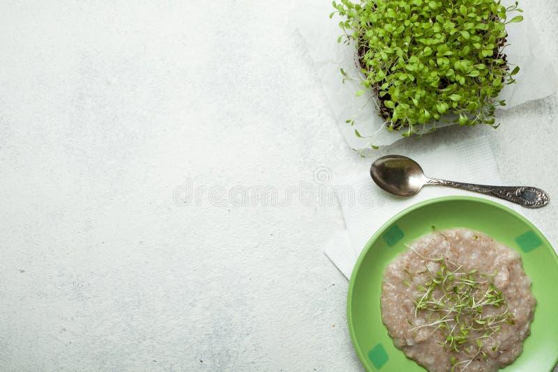 Farinha de aveia em uma bacia verde e em uns micro verdes na mesa de cozinha, vista superior O conceito de reduzir o peso do alim fotografia de stock royalty free
