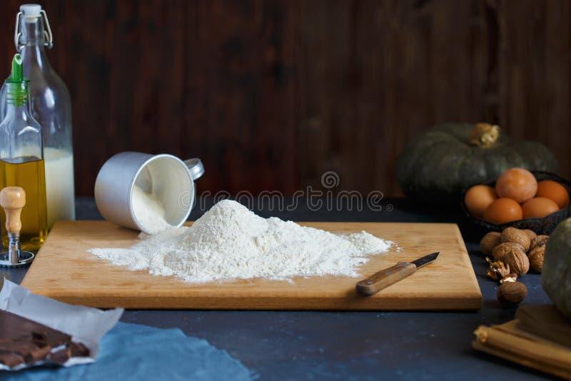 Farinha de cozimento das porcas do leite de manteiga da abóbora dos ovos dos ingredientes em uma tabela de madeira contra um fund foto de stock royalty free