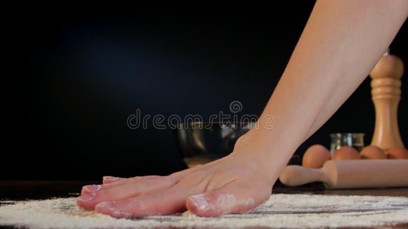 Farinha de espalhamento da mão fêmea na tabela fotografia de stock royalty free