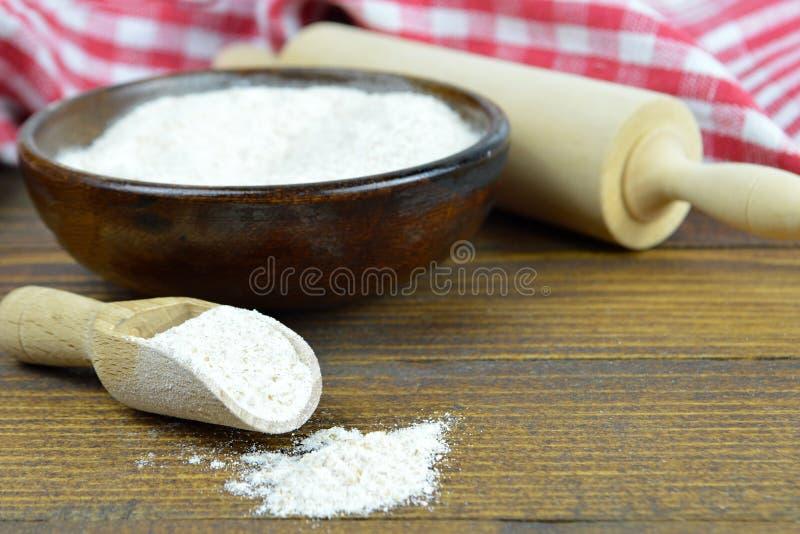 Farinha de trigo inteiro na bacia de madeira, na colher de madeira e no pino do rolo imagens de stock