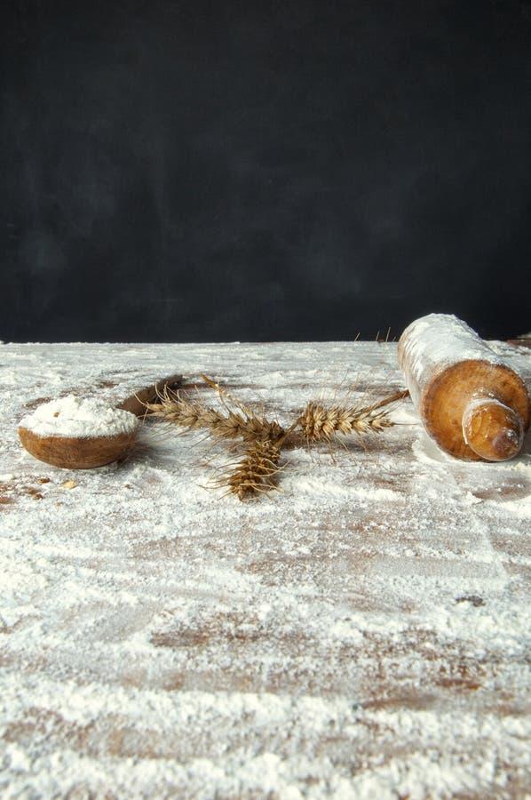 farinha do rolo e uma colher de madeira e orelhas do trigo imagens de stock