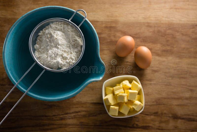 Farinha no stainer com ovos e queijo imagens de stock