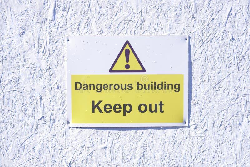Farlig byggnad håller ut att varna varningstecknet på den vita väggen på konstruktionsbyggnadsplatsen royaltyfri fotografi