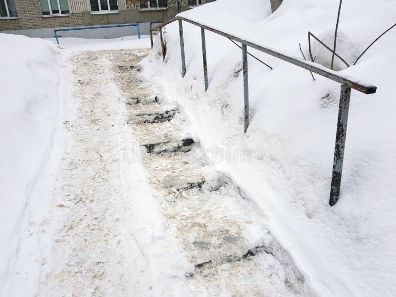 Farlig hal trappa och gammal ledstång i vinter arkivfoto