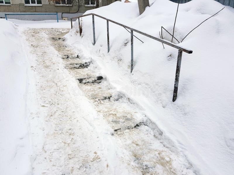 Farlig hal trappa och gammal ledstång i vinter arkivbild
