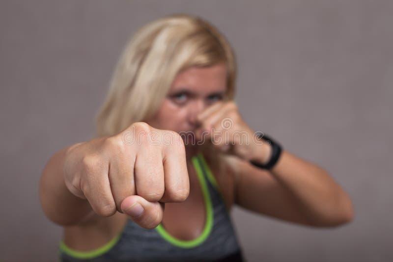 Farlig kvinnlig kämpevisningnäve royaltyfri foto