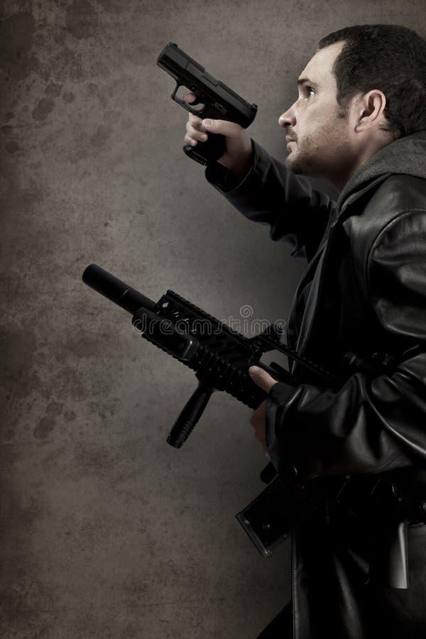 Farlig man som beväpnas med en pistol och en maskingevär arkivbild