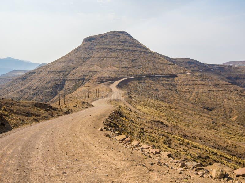Farlig och curvy berggrusväg med brant droppe till dalen, Lesotho, sydliga Afrika royaltyfria bilder
