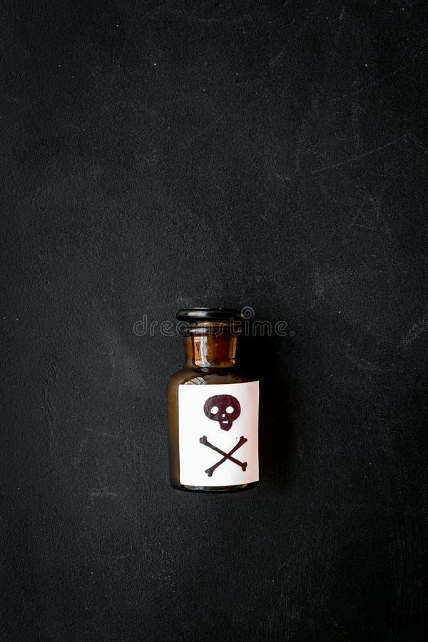 Farliga böjelser, farlig underhållning gift Flaska med skallen och korslagda benknotor på bästa sikt för svart bakgrund arkivfoto