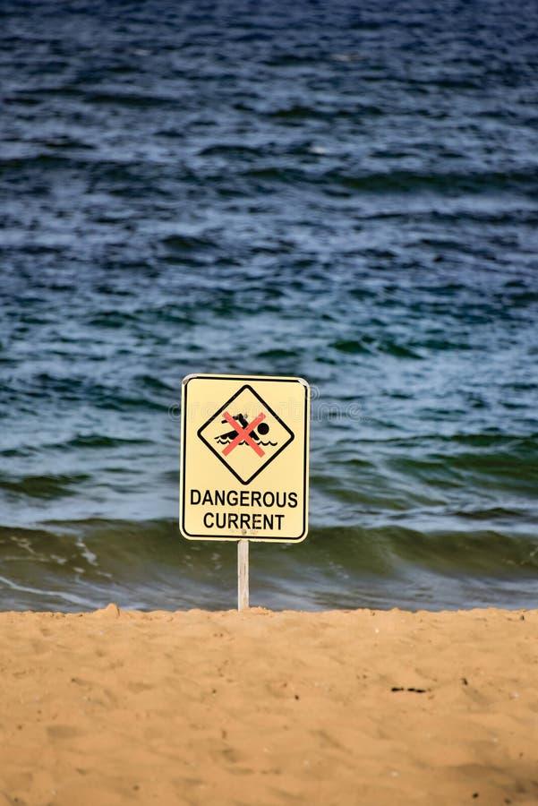 Farligt aktuellt tecken på stranden arkivfoto