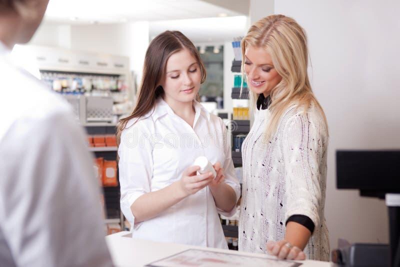 Farmácia fêmea de Advising Customer At do farmacêutico fotografia de stock