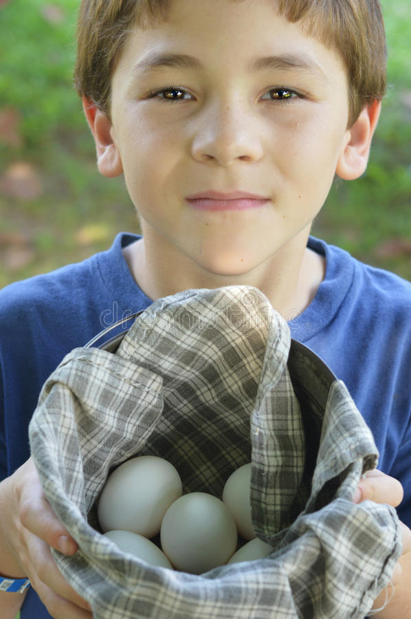 Farm Boy With Fresh Eggs. A young farm boy shows off his fresh eggs that he gathered from the hen coop stock image