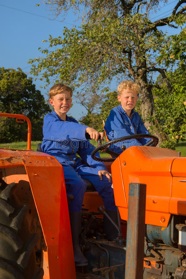 Farm Boys with tractor. Farm boys riding on orange tractor stock photography