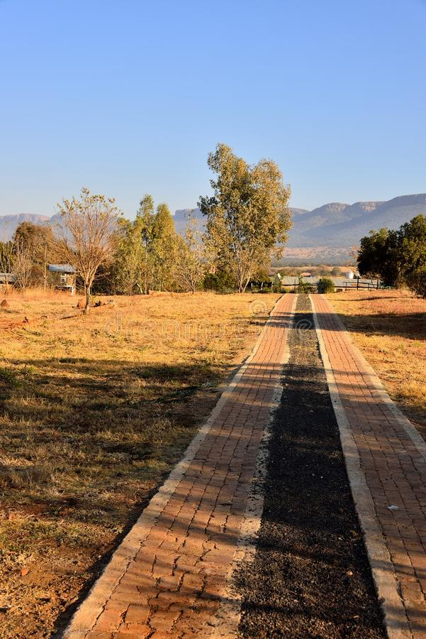 Farm Driveway. Driveway leading to holiday chalets on farm near Skeerpoort South Africa. Magaliesberg mountains and blue skies in backdrop stock photography