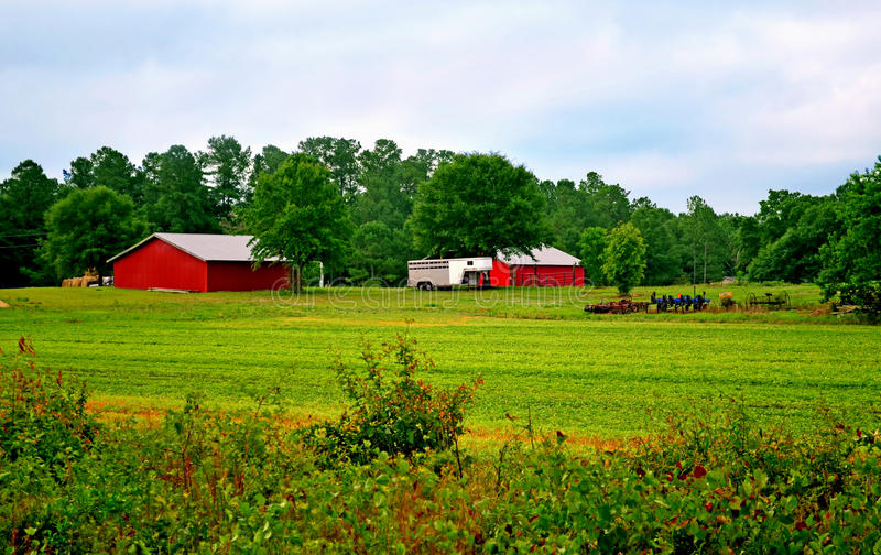 Farm Equipment, Barn, Stable, and Horse Trailer. Big red barn and horse stable sitting in the middle of some farm land with some old farming equipment and horse stock photo