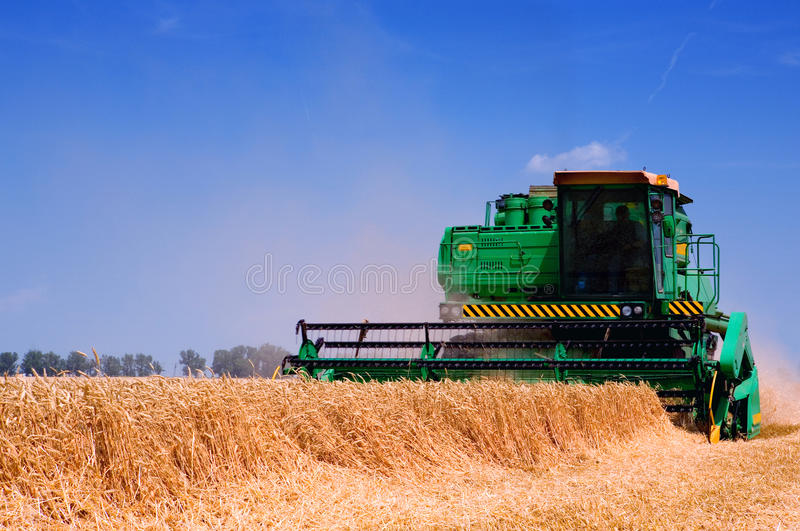 Farm equipment harvester. Green farm equipment harvesting wheat in a field with a blue sky background royalty free stock photos