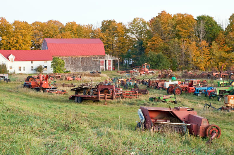 Farm equipment junkyard fall. A junkyard of old, abandoned, rusting farm tractors and heavy duty farming equipment in fall royalty free stock photos
