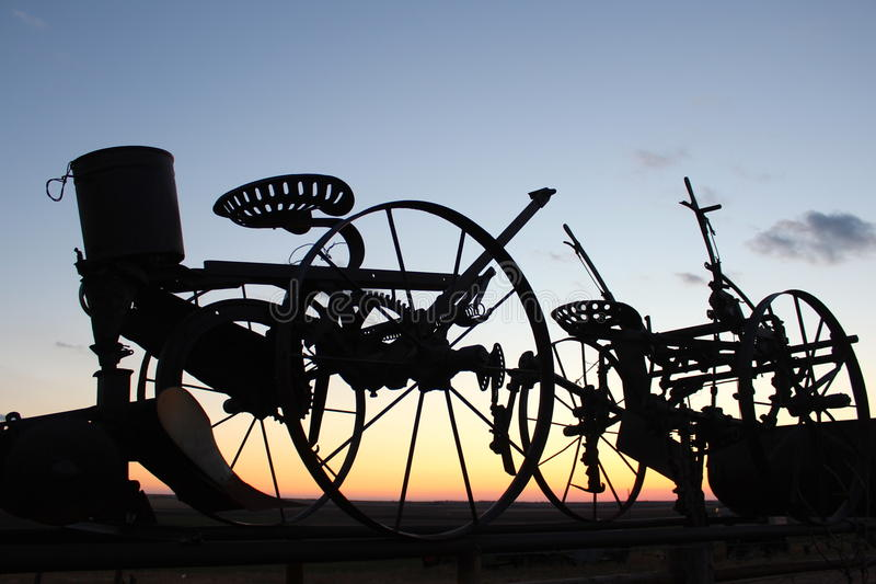 Farm equipment at sunset. Silhouette of antique farm equipment and sunset sky stock photos
