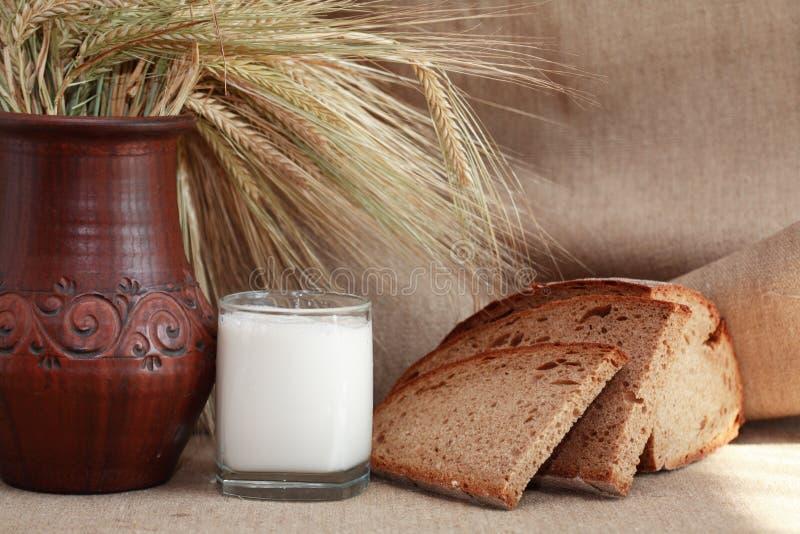 Farm Food. Still life. Bread and milk near wheat on canvas background royalty free stock photos