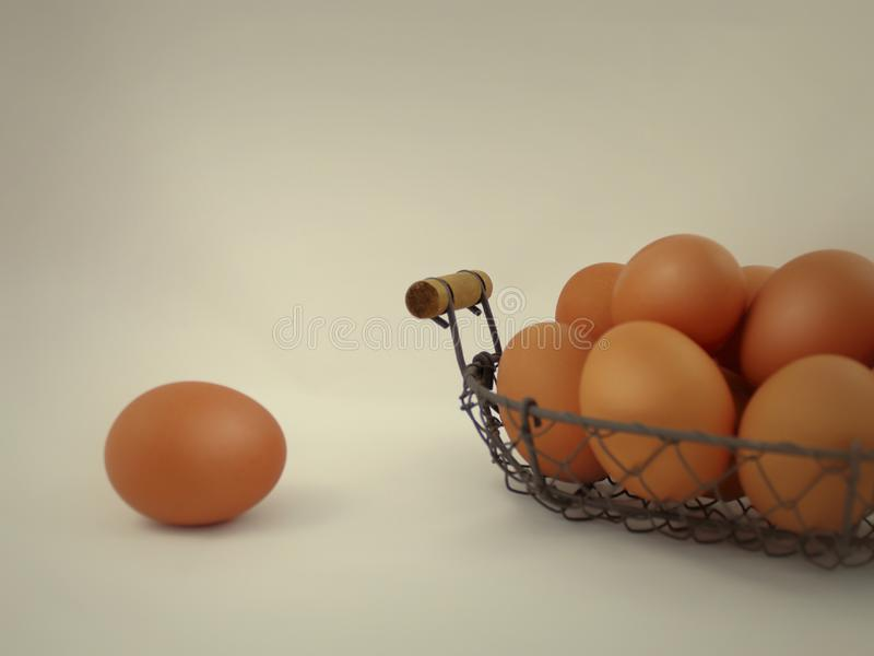 Brown farm fresh eggs in rustic wire mesh basket close-up image on light color background with copy space stock photography