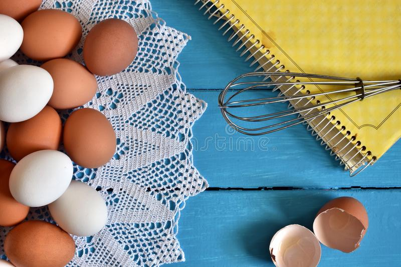 Farm Fresh Organic Eggs. A top view image of farm fresh organic eggs, wire whisk and cookbook on a bright blue background royalty free stock photos