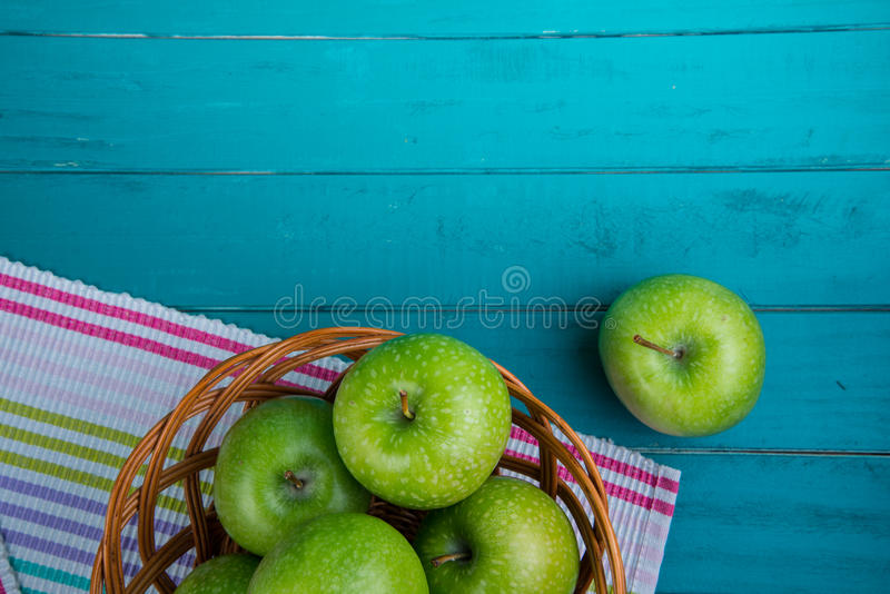 Farm fresh organic green apples in basket on wooden retro blue royalty free stock image