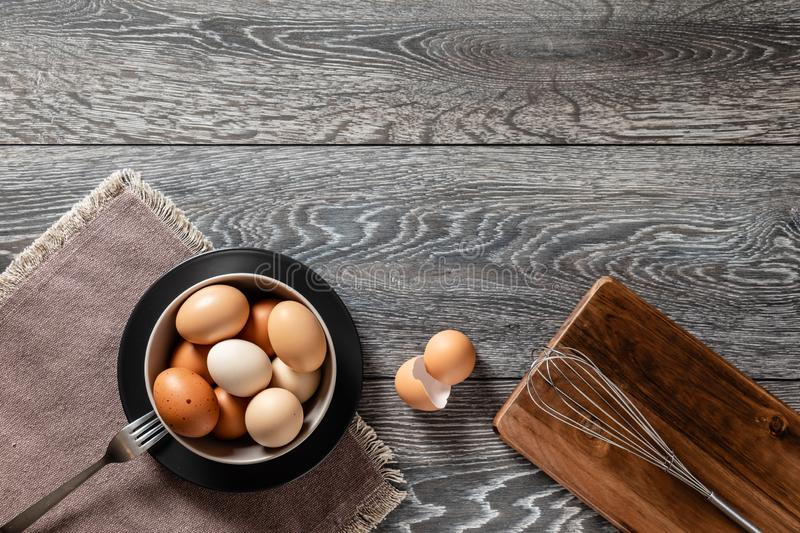 Farm fresh organic large brown and white eggs in bowl on rustic dark oak wood background table. royalty free stock photo