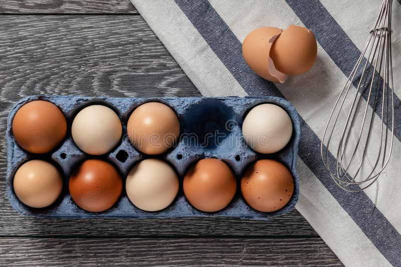 Farm fresh organic large brown and white eggs in egg carton on rustic dark oak wood background table. stock photo