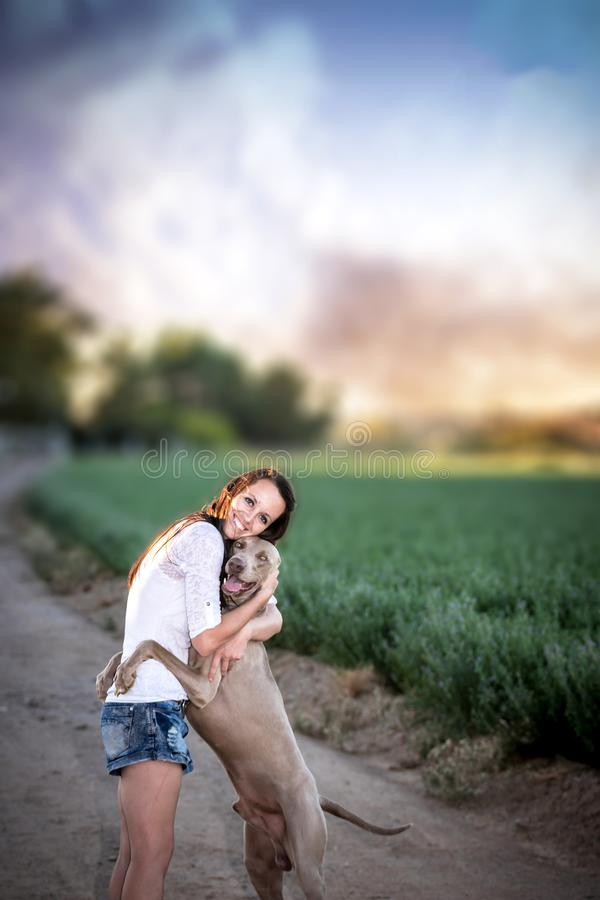 Farm girl and Weimaraner dog on a dirt road. With a dramatic sky royalty free stock photo