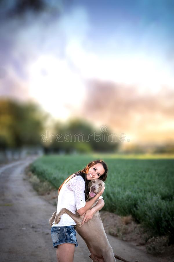 Farm girl and Weimaraner dog on a dirt road. With a dramatic sky stock images
