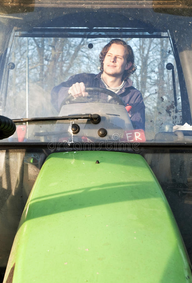 Farm hand. Behind the wheel of a tractor, seen through thge windscreen stock images