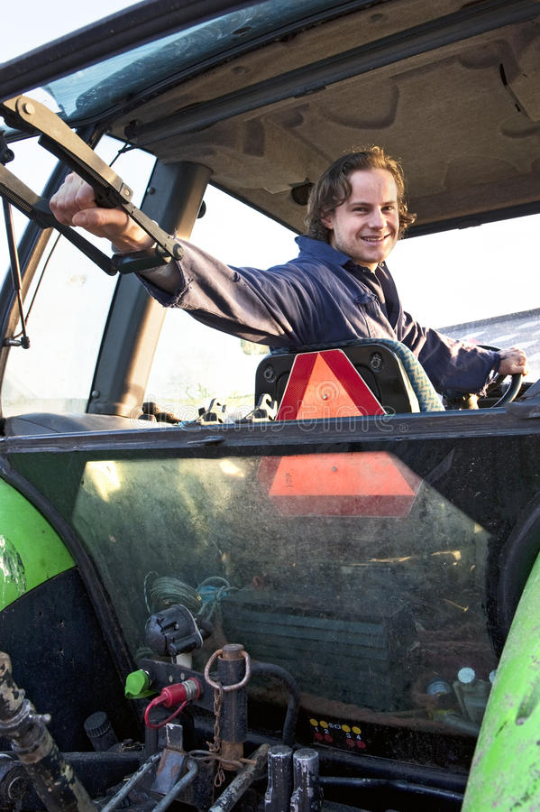 Farm hand in a tractor. Farm hand looking out the rear window of a tractor, hodling the lever stock images