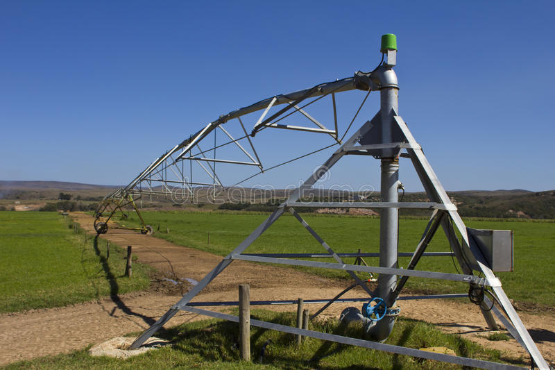 Farm irrigation equipment. With blue skies and green fields stock image